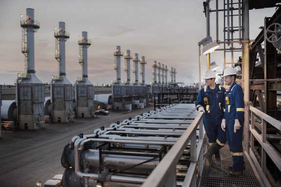 Workers overlooking the stacks in an oil sands facility