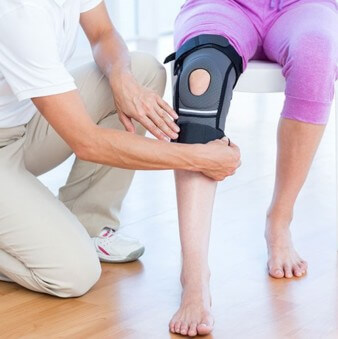 physiotherapist applying a knee brace to a patient