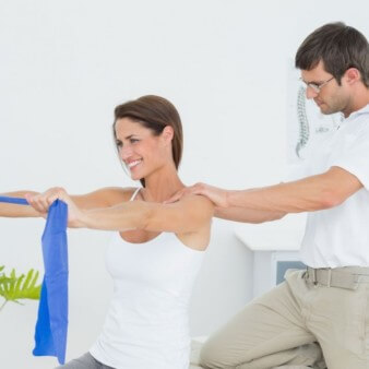 physiotherapist assisting patient with resistance band shoulder exercise