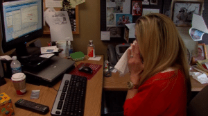 A woman blowing her nose at her desk