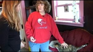 Marie Glover pets one of the cats at Tabbytown