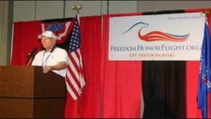Chuck Hanson at a podium talking about the Freedom Honor Flight
