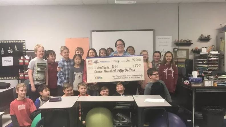 Students at Sand Lake Elementary hold a check from the Tools for School program