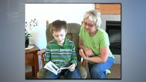 Nancy Herbers helping a child read a book