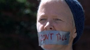 woman wearing duct tape over mouth with don't tell written on duct tape in red marker