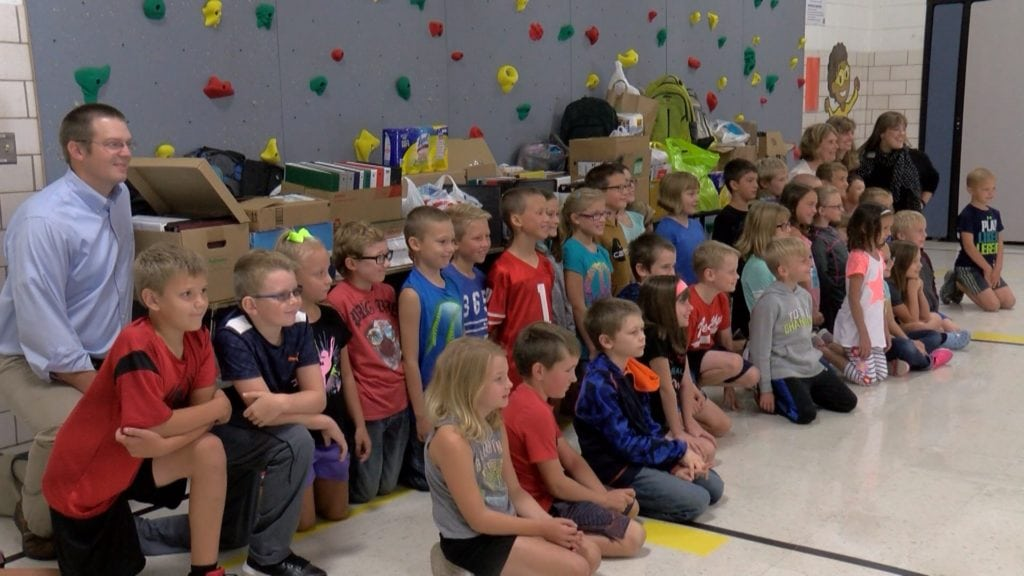 Elementary school children sit for a picture in front of donated school supplies