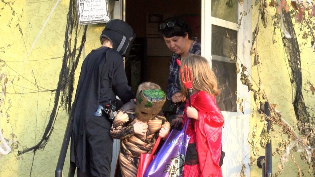 Resident hands candy to young visitors