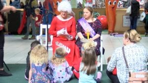 Mrs. Claus reads to a group of children.