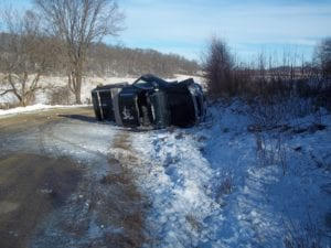 Truck is flipped on its side with the roof cut open after a rollover accident.