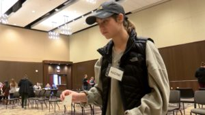 Student shows off ID as part of the reentry simulation.