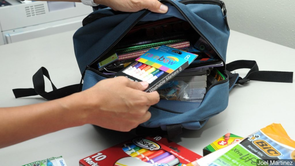 Person placing school supplies in a backpack
