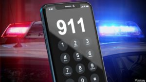 smartphone dialing 911 with police car lights in background