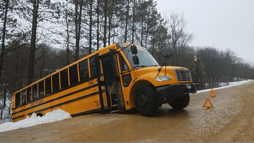Bus stuck in a ditch on 65th St. NE, another bus perpendicular on a road in SW Rochester