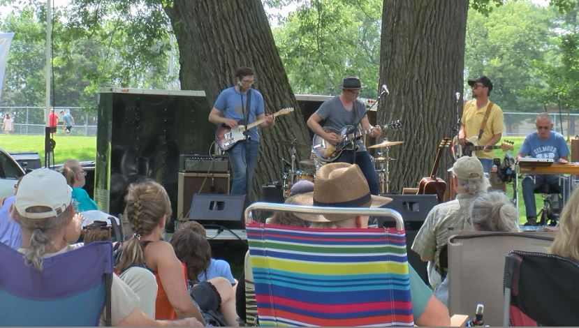 People listen to live music in Cooke Park.