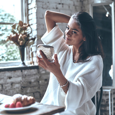 Looking great. Attractive young woman looking in the mirror while having breakfast at home