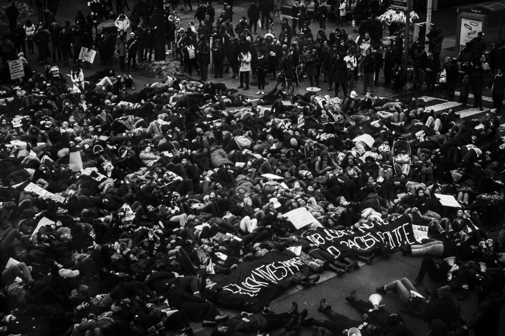 Jalani Morgan, Black Lives They Matter Here (The power of symbolism: protesters perform a 'die-in' by laying on the ground at Yonge and Dundas Square in Toronto. This was in soli- darity and in rage of the decision of the New York grand jury to not indict the police officers responsible for the murder of Eric Garner), Toronto, Canada., 2014. Inkjet print on vinyl, 8.7x6.5