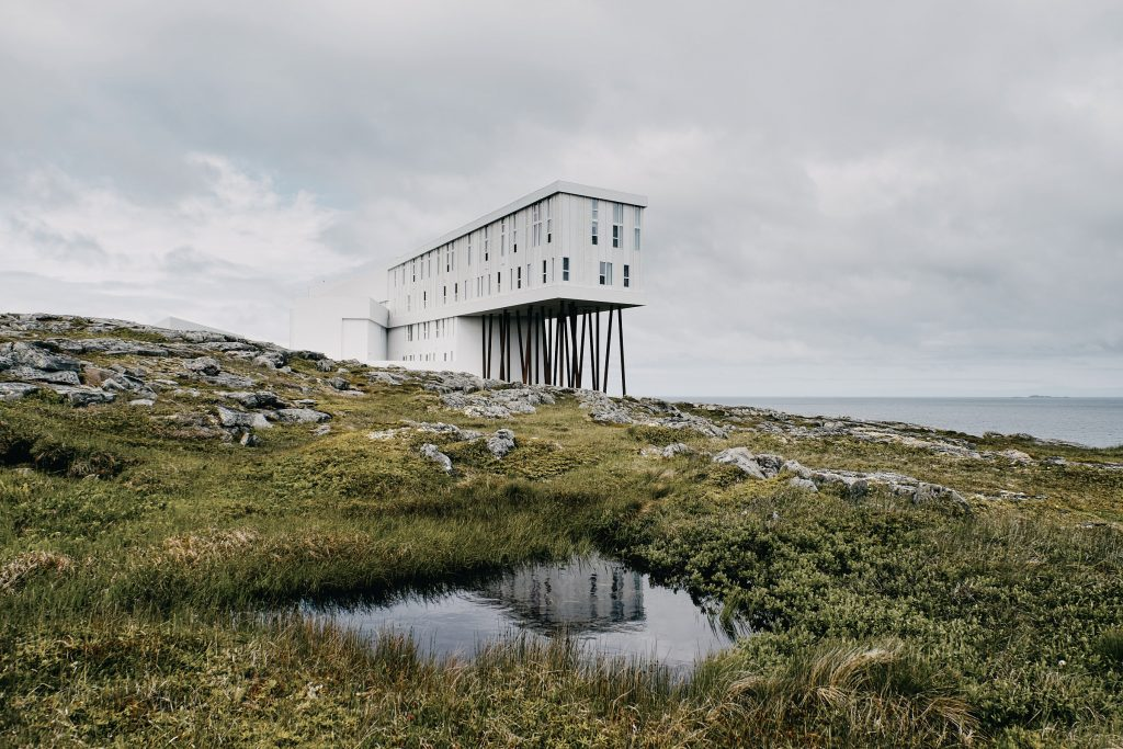 A modern-design, white hotel sits perched on the rocky shore, surrounded by a grassy field, looking out towards the ocean.