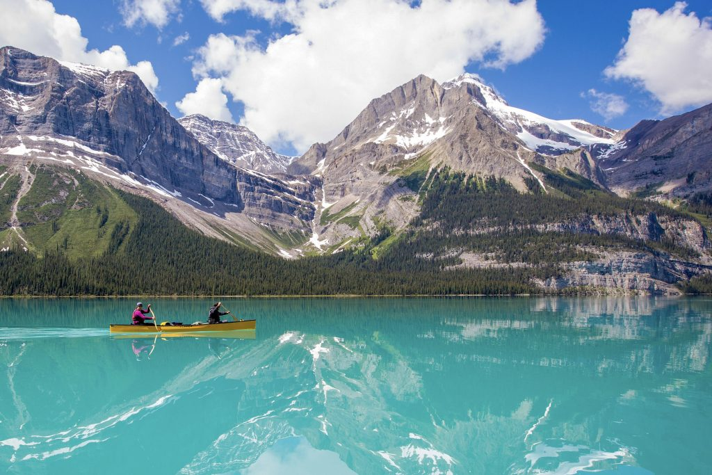 a group of people boating on maligne lake in a canoe and a kayak