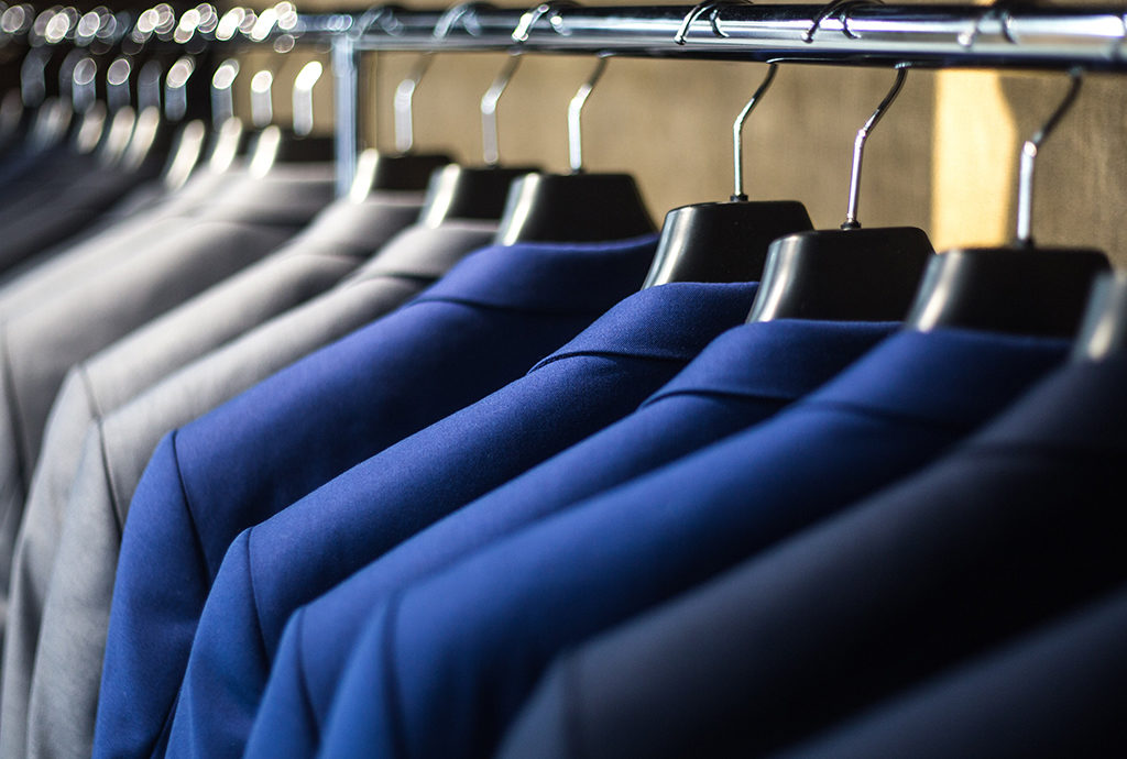 full closet of blue and grey suits