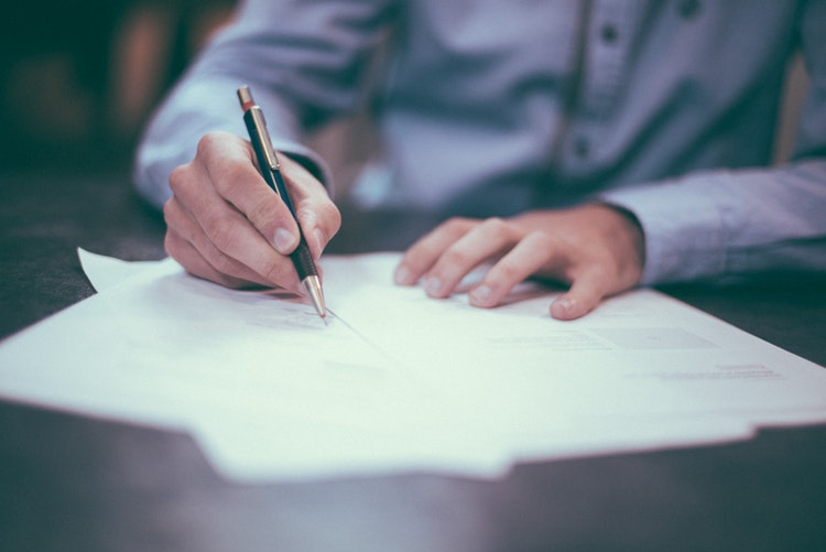 Photo of a man signing documents