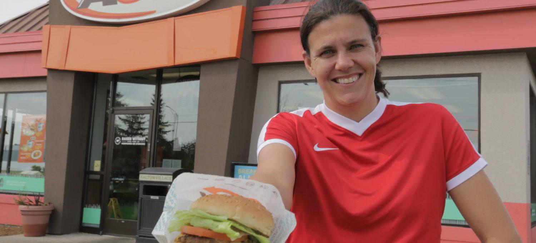 Photo of Christine Sinclair holding an A&W burger