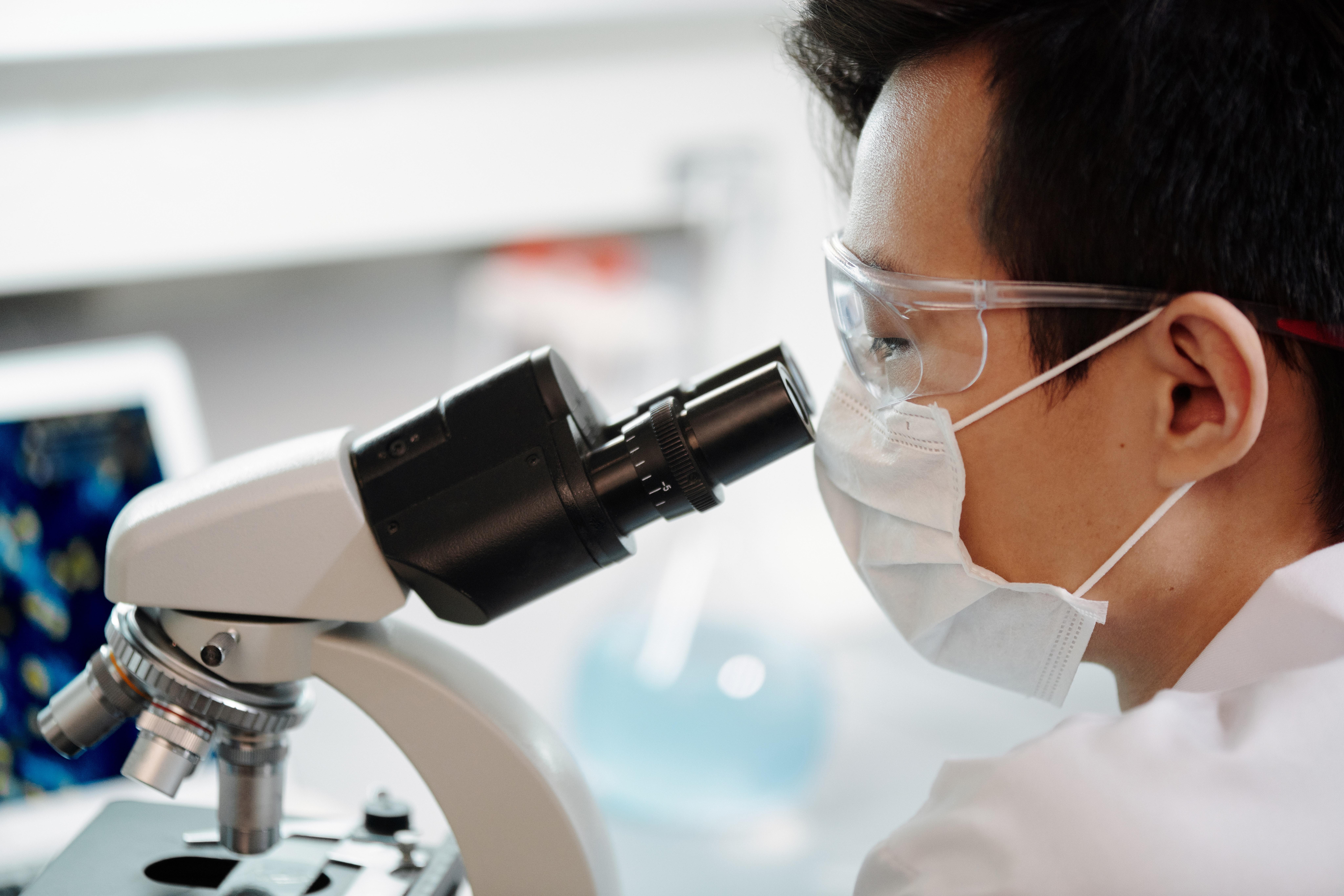 Scientist look into microscope
