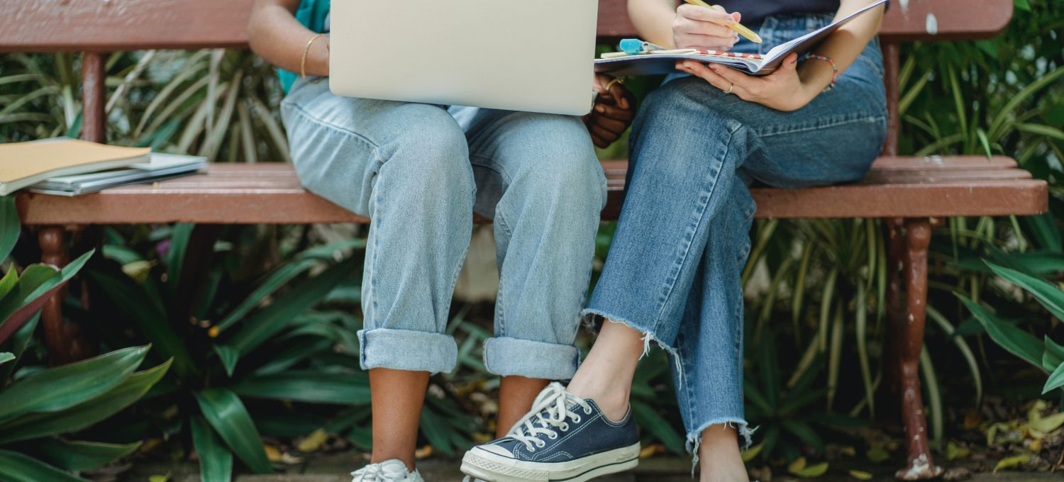 Photo of two women sitting on a bench with a latop and notebook on their lap