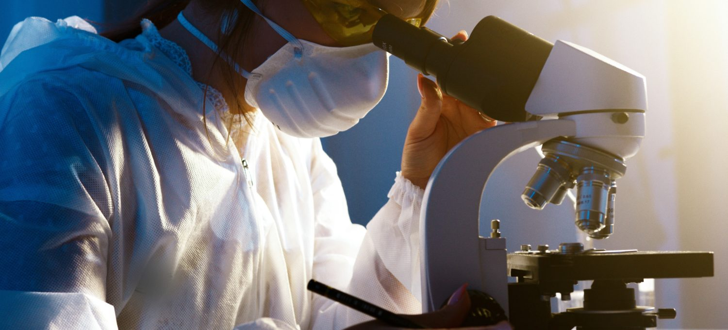 Photo of scientist looking into microscope
