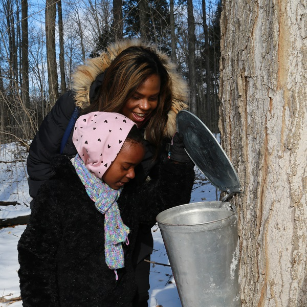 mother and daughter participate in sugarbush maple syrup festival at bruces mill conservation park