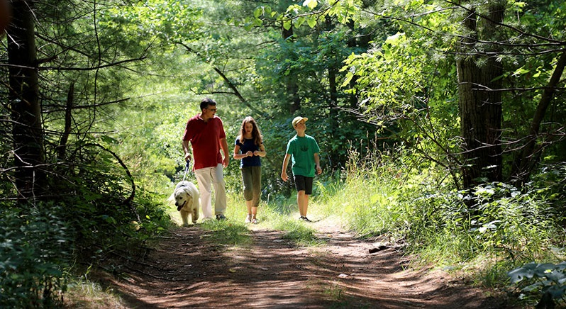 family walking dog on nature trail