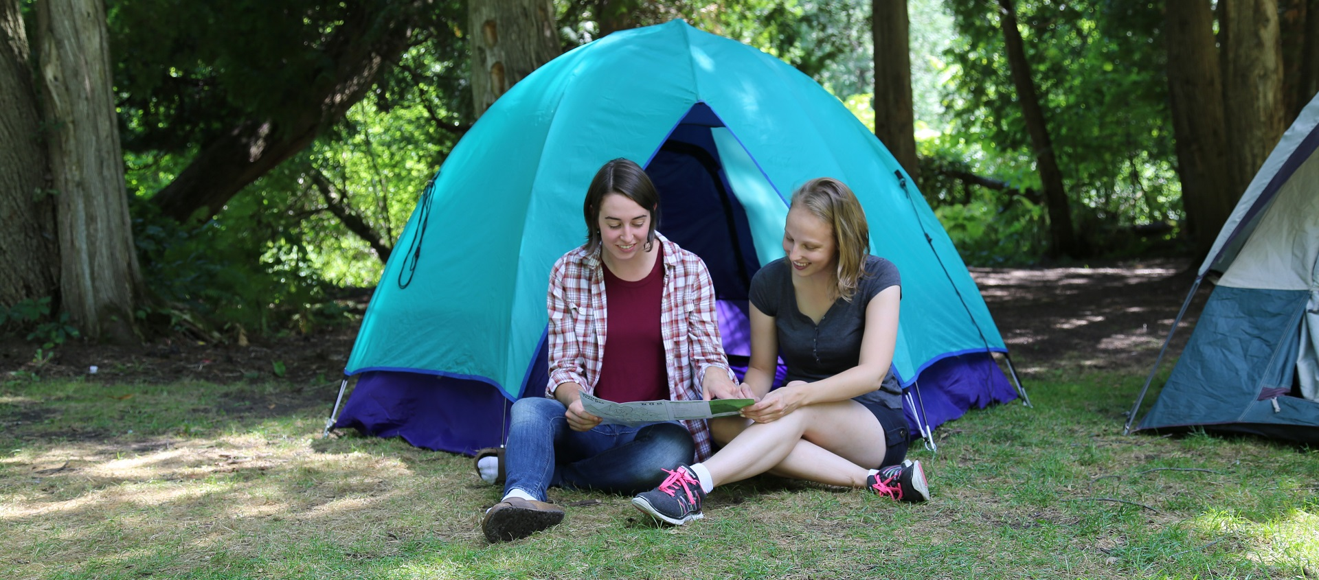 young women sit in front of tent at Albion Hills Campground