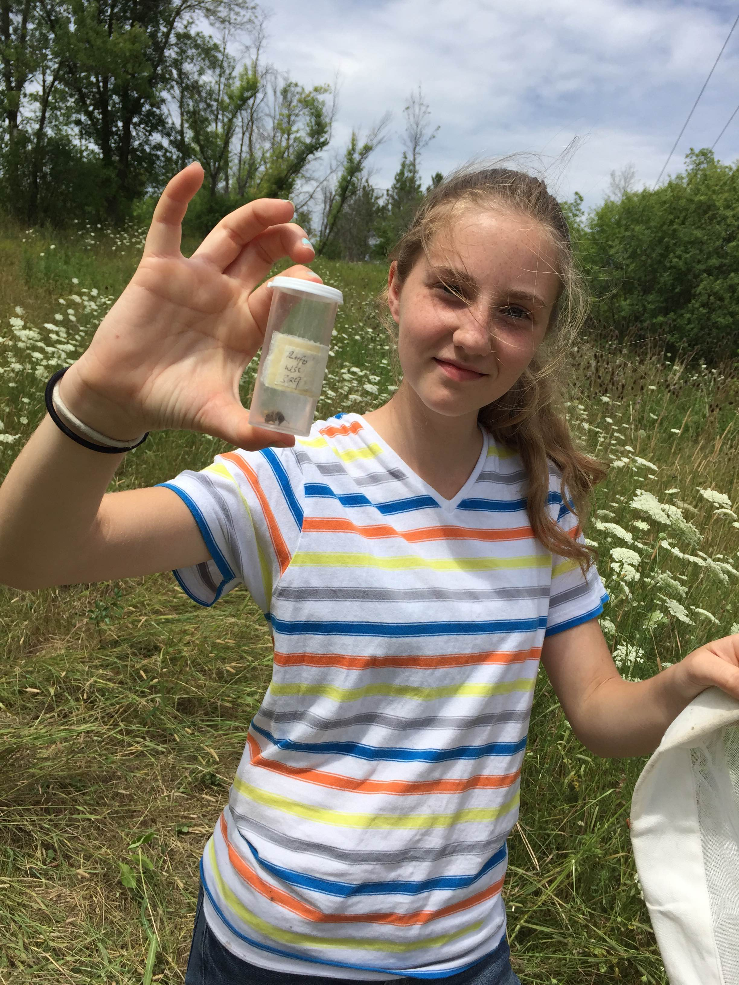 Young woman holding up vial with bee specimen