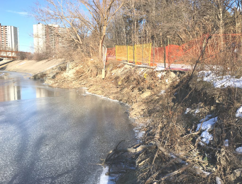 Looking upstream at bank erosion on right side and temporary fencing along eroded trail.