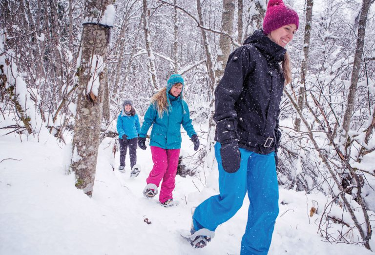 Women snowshoeing through a forest in winter