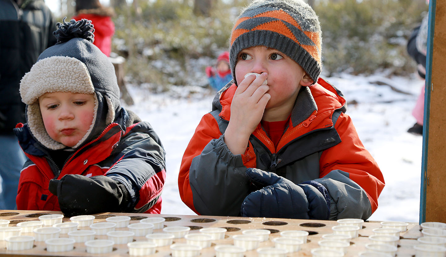 youngsters sample maple syrup at the Sugarbush Maple Syrup Festival