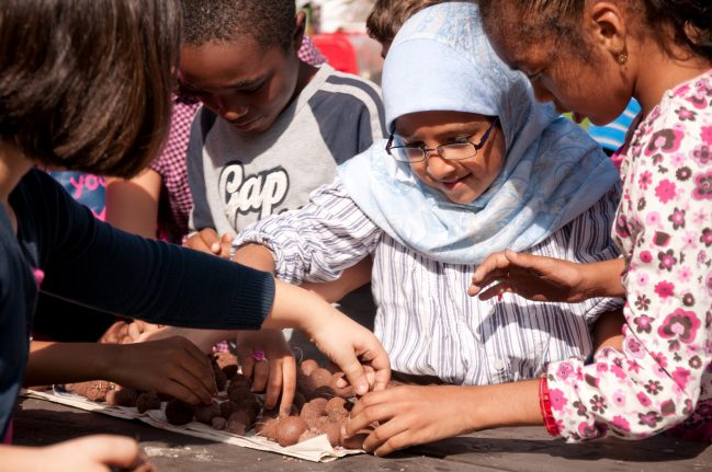 Group of children choosing from a table of seedballs