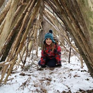 girl kneels in shelter at Claremont March Break camp