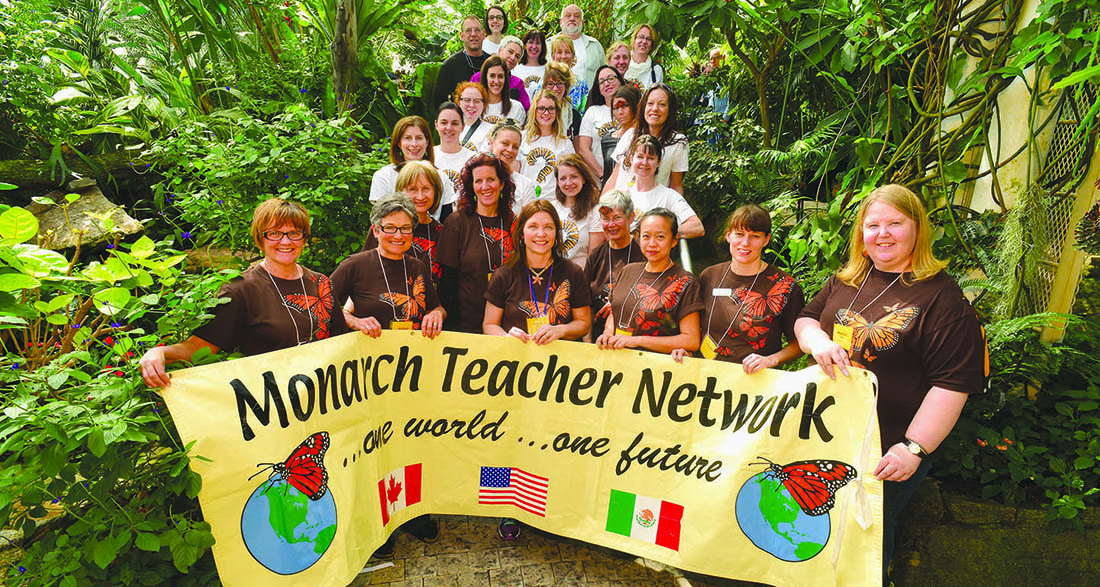 Monarch Teacher Network volunteers hold banner