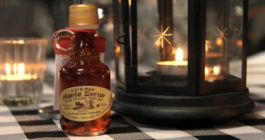 A bottle of maple syrup next to a candle