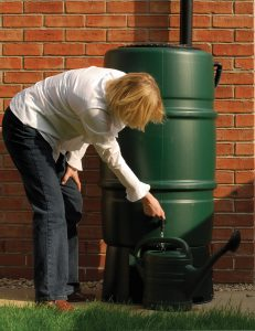 A person collect rainwater from the rain barrel