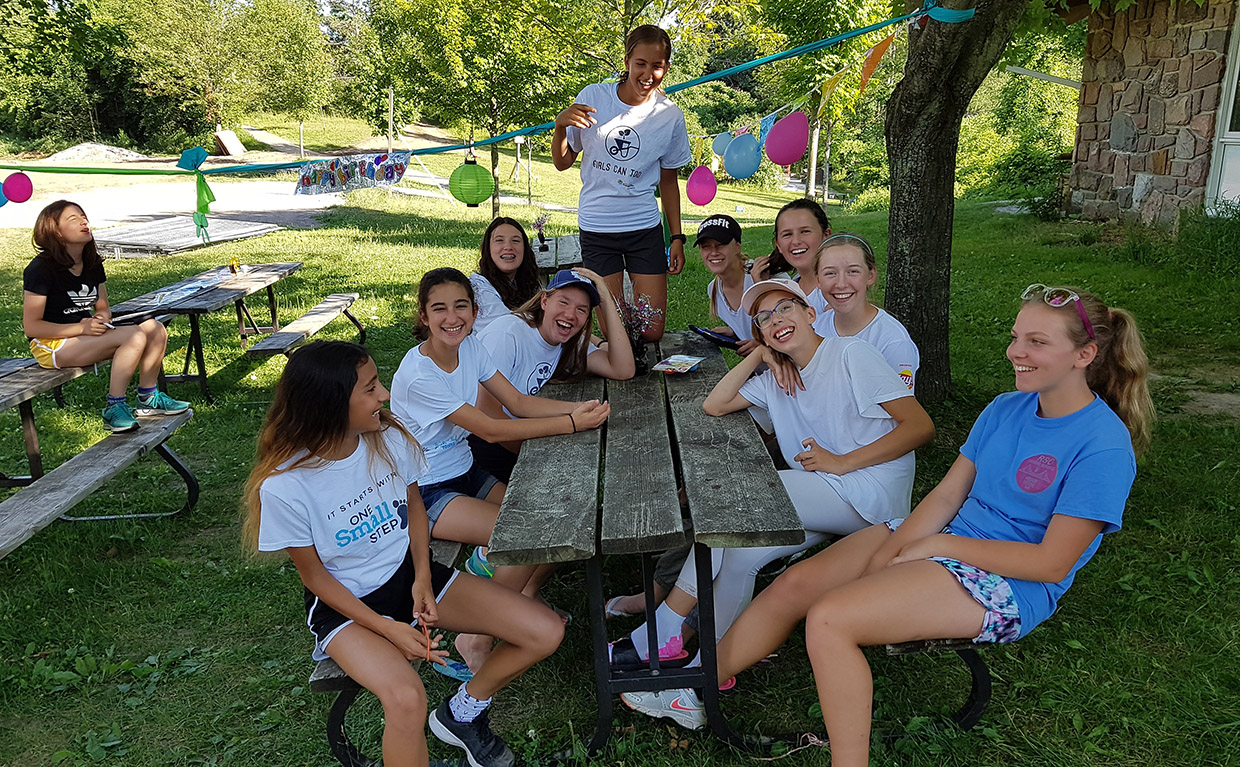 girls gather around picnic table at Albion Hills Field Centre summer camp