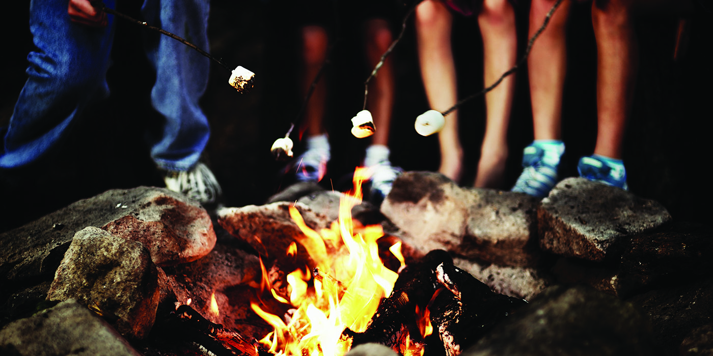 children roasting marshmallows over campfire