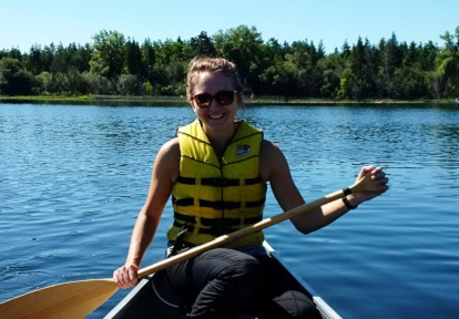 young woman paddles canoe on Lake St George