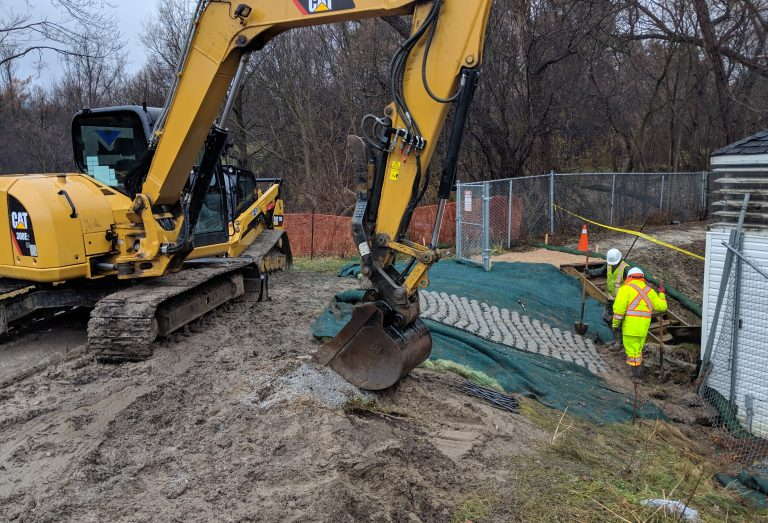 Excavator installing a vegetated stone erosion control mat for bank stabilization works in Pomona Mills Park