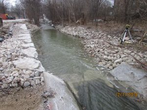 Photo of a single-tier armourstone wall on the left bank of Etobicoke Creek with a cobblestone channel on the right bank of the Creek. A preexisting concrete channel is located further upstream.