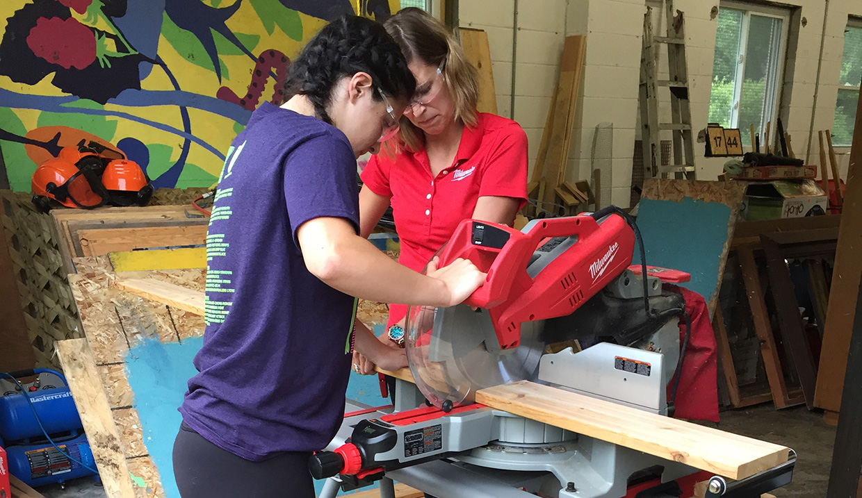 young woman in Girls Can Too program operates circular saw