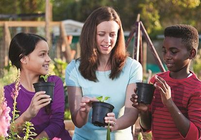woman and children planting pollinator habitat