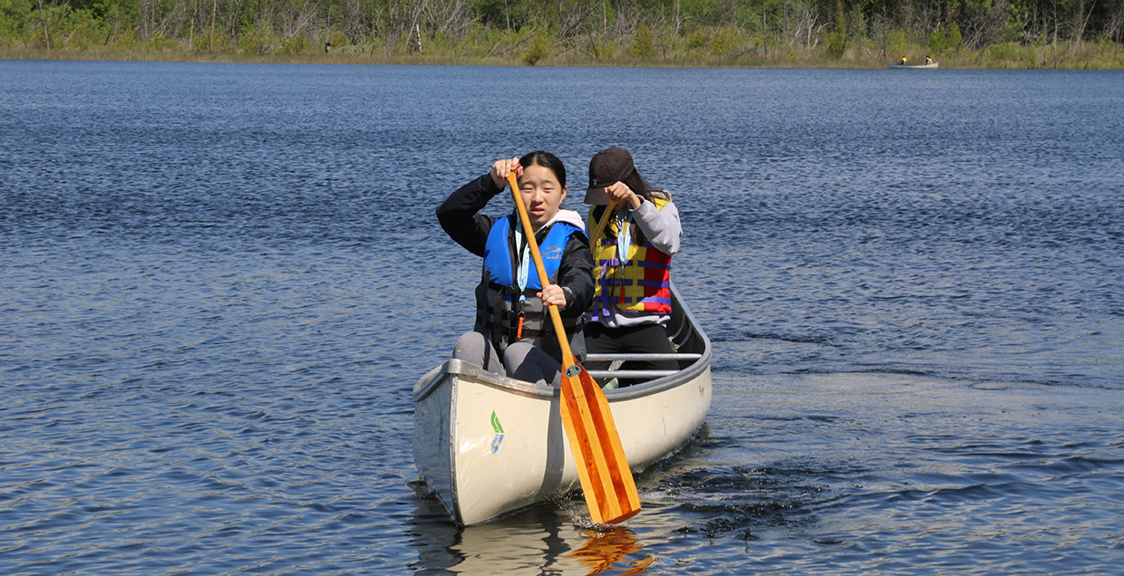 girls canoeing at Lake St George summer camp