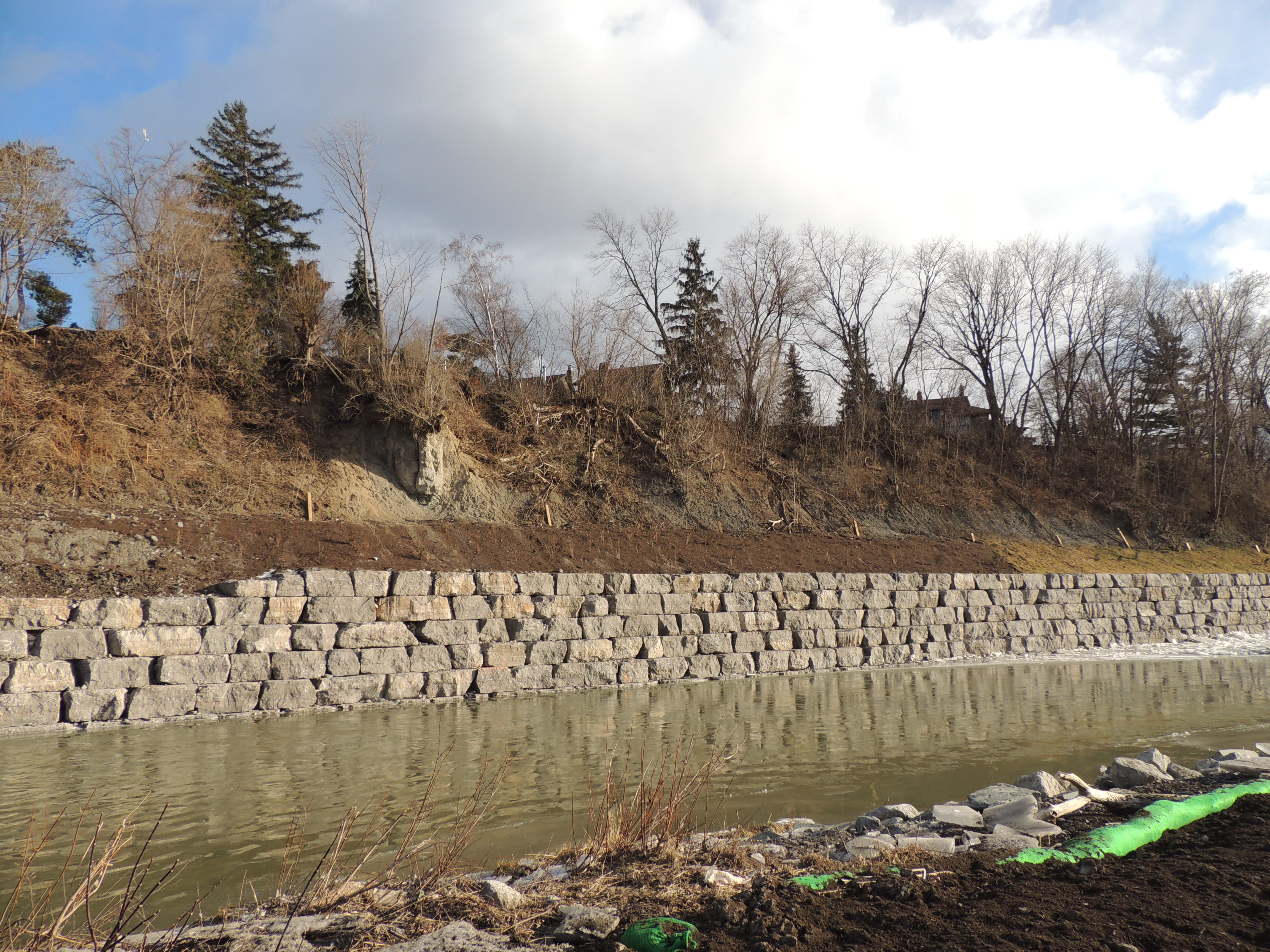 An armourstone wall and soil stabilization measures at the toe of a steep slope overlooking the Humber River