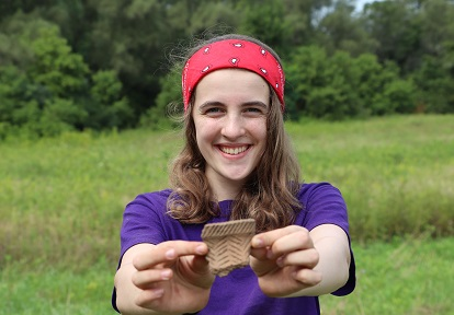 female student holds artifact uncovered during Boyd Archaeological Field School excavations